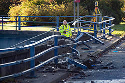 © Licensed to London News Pictures. 27/10/2019. Salford, UK. A police officer surveys the scene amidst the damaged crash barrier . A car lies on its side on a pedestrian walkway at the Pendleton Roundabout on Broad Street in Salford . Members of the public pulled a man and a woman from the wreckage after a BMW car crashed through a barrier and landed on a pedestrian walkway below . Their condition is unknown and police , paramedics and fire crews are at the scene . Photo credit: Joel Goodman/LNP