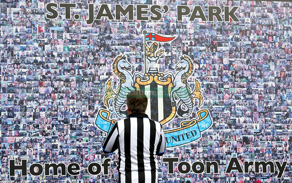 A Newcastle United fan looks at a tribute wall ahead of the Premier League match at St James' Park, Newcastle.
