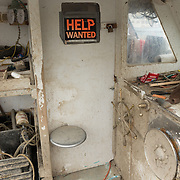 Gloucester, MA USA, April 14, 2015. Help wanted sign on an old lobster boat in the harbor.