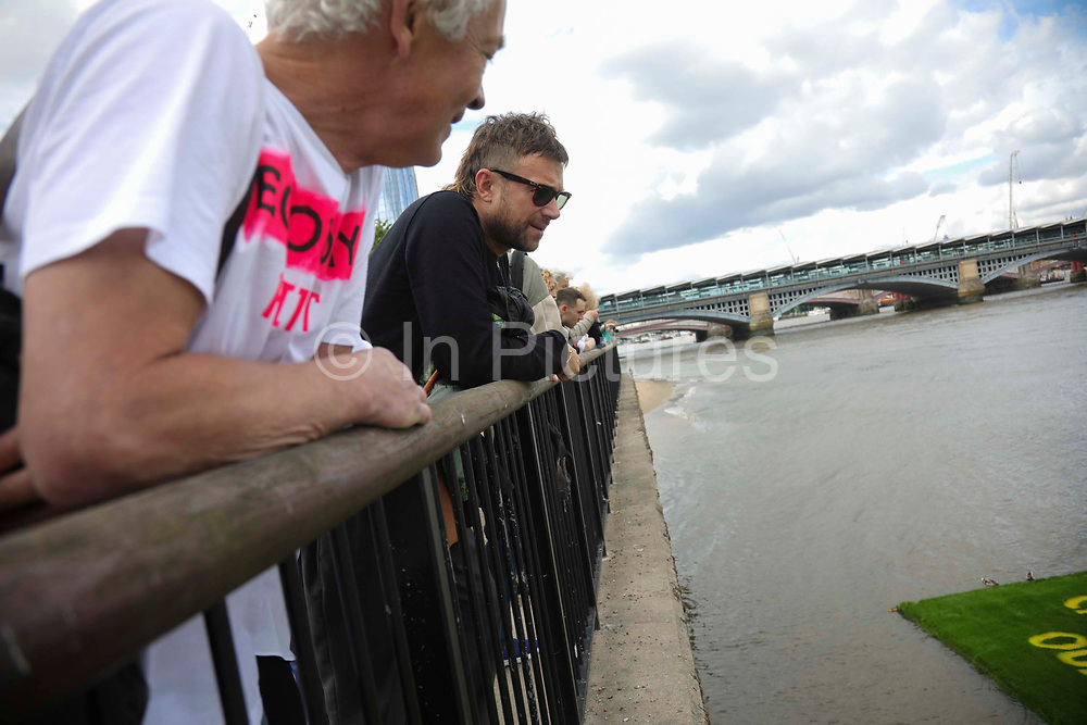 Art work by Ackroyd & Harvey made in grass with words by Ben Okri is set to float on the rising tide on the Thames on the 25th of June 2021, Central London, United Kingdom. The message is a call for action to save the planet from climate change catastrophe. Artist Dan Harvery shows singer Damian Albarn the finished art work afloat. The art work was moved by activists and laid onto a raft on the Thames as the tide was rising. The event marks the launch of XR Writers Rebel's Paint the Land project, which teams acclaimed writers and artists to create landscape graffitos drawing attention to the climate and ecological emergency. The Speakers at the event included the artist Ackroyd & Harvey, writer Ben Okri, Kelly Hill and Simon Bramwell, co-founder of Extinction Rebellion.  The event finished with a song by Damon Albarn and Mirabella Okra and the Capital Choir.