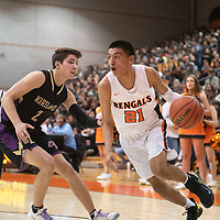 Gallup Bengal Jeffrey Yazzie (21) drives to the basket as Kirtland Central Bronco Ty Jenks (2) defends in Friday night's district 1-4A tournament championship game against Kirtland Central Broncos at Gallup High School in Gallup. The Bengals beat the Broncos 60-41.
