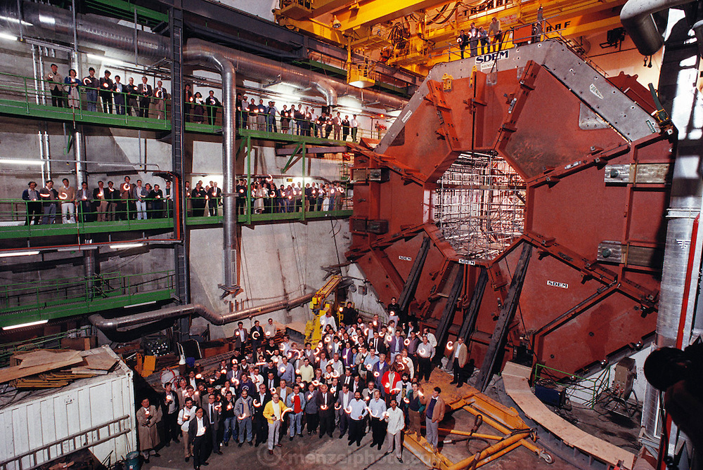 The particle physics collaboration group in the detector pit of the L-3 experiment at CERN's Large Electron-Positron Collider (LEP) ring during its construction in [1988] (Sam Ting bottom left in trench coat.) The pit now contains detectors that can measure and identify the various electrons, muons and photons that are emitted following collision events. The main part of the detector is the large magnet, contained in a cubic space of 12 meters each side and weighing 7810 tons. The magnet surrounds the particle detectors; the vertex chamber, the electromagnetic calorimeter, the hadron calorimeter and the muon chamber. The LEP ring was inaugurated on 13 November 1989. The LEP ring was inaugurated on 13 November 1989. [1988].