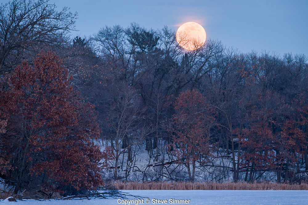 At Lebanon Hills Regional Park in Eagan, MN. Jensen Lake offered a long view to the moonrise.  I was about 1/3 mile from the shoreline. Using a telephoto lens gives a perspective that makes the moon larger in the frame.
