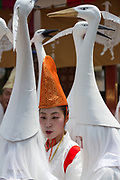 A young Shinto priestess talks with young women dressed as herons take part in the Daigyoretsu or Grand on  first day of the three-day Sanja Matsuri, Asakusa, Tokyo, Japan. Friday May 18th 2018. The Sanja matsuri, or festival, takes place over the third weekend of May in the streets around the famous Senso-ji Temple. It lis one of the biggest festivals in Japan and lasts for three days  (May 18th to May 20th) with parades of large mikoshi, or portable shrines, carried around the streets by crowds of supporters