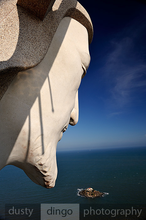 "Face of ""Christ of Vung Tau"" overlooking Hon Ba Island and the South China Sea beyond. ""Christ of Vung Tau"" is a statue of Jesus standing on Nui Nho (Tao Phung, or Little Mountain), in Vung Tau. Built between 1974 and 1993, it is 32 metres (105 ft) high, standing on a 4 metre (13 ft) high platform, for a 36 metre (118 ft) total monument height, with two outstretched arms spanning 18.3 metres (60 ft). There is a 133-step staircase inside the statue leading to observation points on both shoulders. Vung Tau, Vietnam"