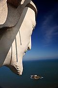 """Face of """"Christ of Vung Tau"""" overlooking Hon Ba Island and the South China Sea beyond. """"Christ of Vung Tau"""" is a statue of Jesus standing on Nui Nho (Tao Phung, or Little Mountain), in Vung Tau. Built between 1974 and 1993, it is 32 metres (105 ft) high, standing on a 4 metre (13 ft) high platform, for a 36 metre (118 ft) total monument height, with two outstretched arms spanning 18.3 metres (60 ft). There is a 133-step staircase inside the statue leading to observation points on both shoulders. Vung Tau, Vietnam"""
