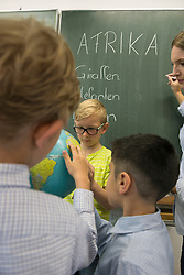 Female teacher and students looking at globe in classroom, Munich, Bavaria, Germany