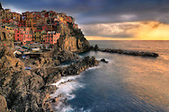 The Cinque Terre, famous worldwide for their five enchanted medieval villages with small fishermen ports, narrow cobblestone lanes and romantic trails, are also a gold mine of landscape photography opportunities.And Manarola, with its colourful fishermen's houses clinging onto the rugged cliffs and its tiny port, is probably the most pictoresque among the five villages. I took this picture on a  evening of January, at the end of a rainy and windy day. The wind was calming down after the storms and the last rays of the setting sun was bathing the coast with beautiful warm tones.