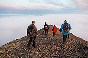 Rafal Flieger (l-r), Lukasz Flieger, Magdalena Puczko, and Grzegorz Karasinski take time off from work at the Polish Polar Station to hike the narrow ridge of Ariekammen for sunset views over Hornsund, Svalbard.