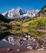 The Maroon Bells and yellow aspen leaves reflect in Maroon Lake. The Maroon Bells are two adjacent peaks of the Elk Mountains: Maroon Peak 14,163 feet on left, seen behind North Maroon Peak 14,019 feet, in Maroon Bells-Snowmass Wilderness of White River National Forest. The mountains are on the border between Pitkin County and Gunnison County, about 12 miles southwest of Aspen, in Colorado, USA. This image was stitched from multiple overlapping photos.