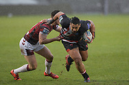 Pauli Pauli (12) of Salford Red Devils looks for a way past Ethan Havard (21) of Wigan Warriors