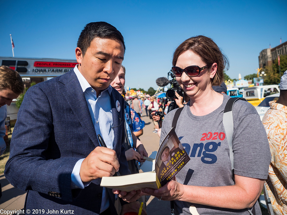 09 AUGUST 2019 - DES MOINES, IOWA: ANDREW YANG autographs his book while he walked through Iowa State Fair Friday. Yang, an entrepreneur, is running for the Democratic nomination for the US Presidency in 2020. He spoke at the Des Moines Register Political Soapbox at the Iowa State Fair Friday. Iowa hosts the the first election event of the presidential election cycle. The Iowa Caucuses will be on Feb. 3, 2020.        PHOTO BY JACK KURTZ