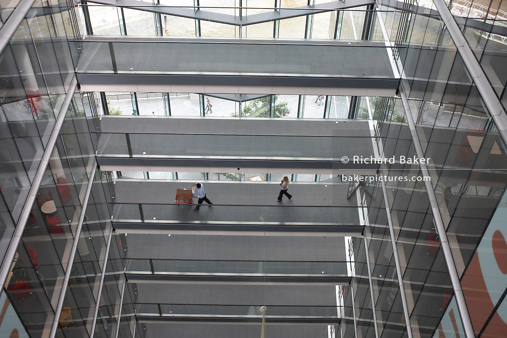 Employees of an auditing company stride along lower middling walkways at the company's London headquarters.