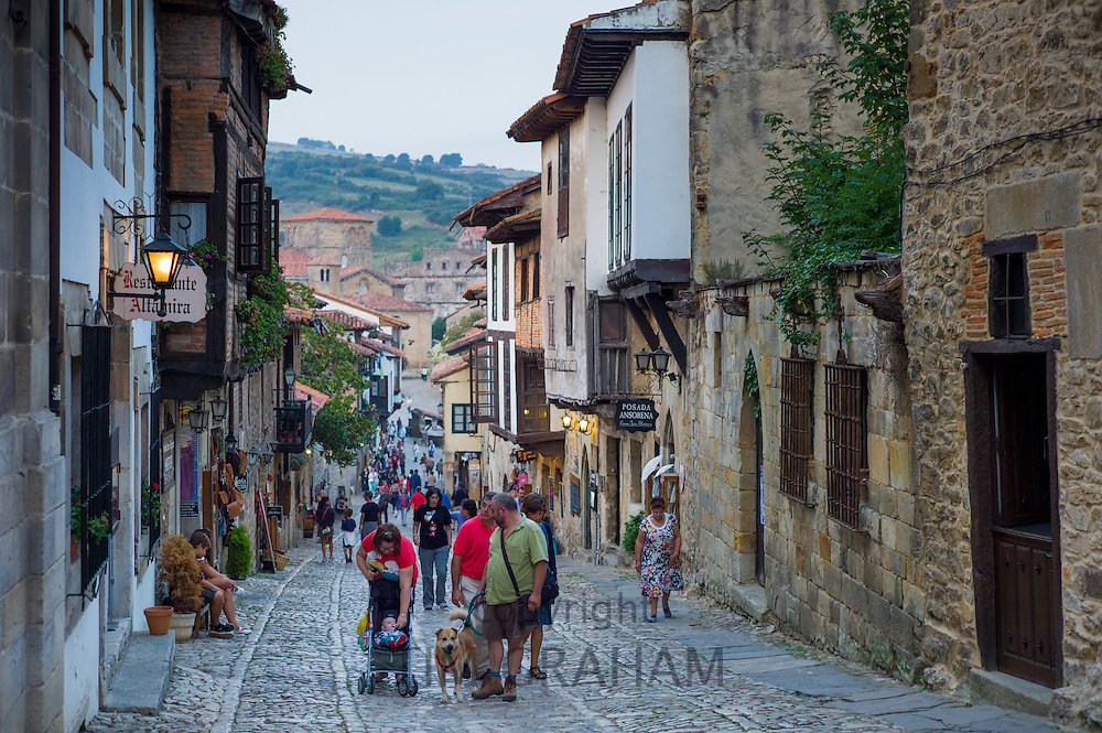 Tourists and residents pass medieval houses in cobbled street of Calle Del Canton in Santillana del Mar, Northern Spain