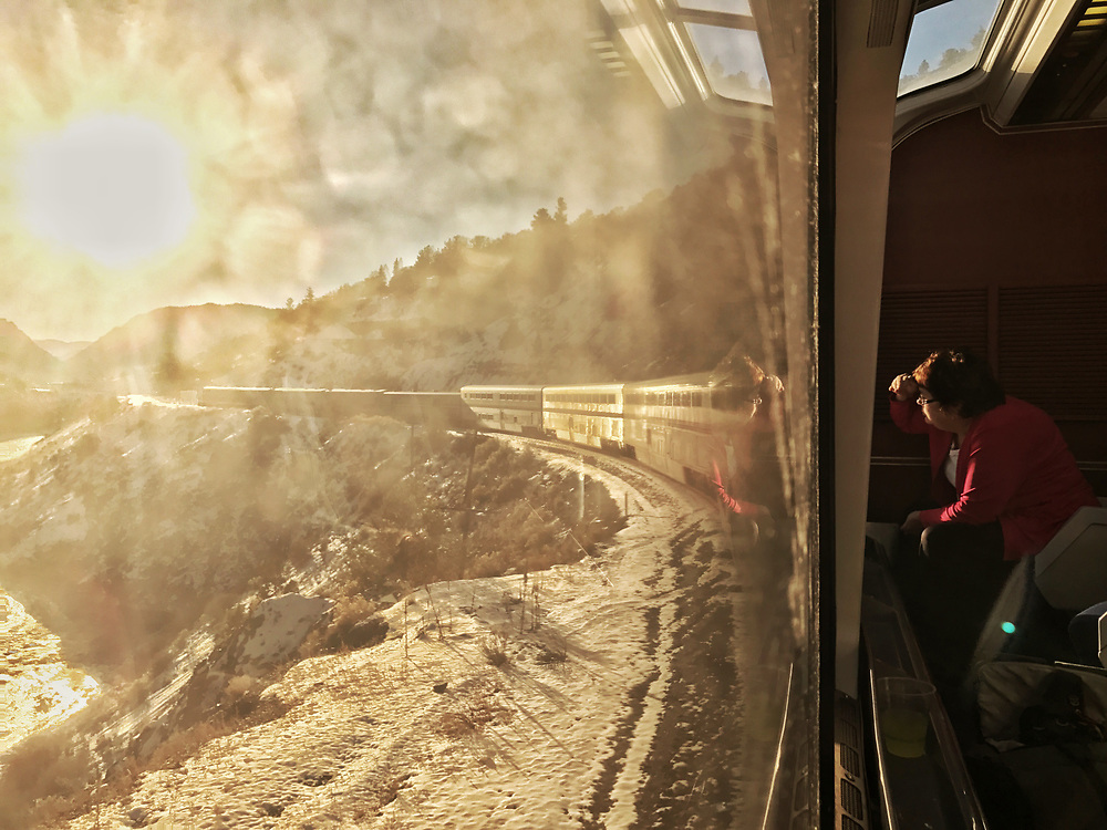 Indiana resident Becky Schulze gazes out the window of Amtrak's westbound California Zephyr train near Kremmling, Colo. as the sun dips toward the horizon on Tuesday, Dec. 20. Schulze said she's in hour #36 on her trip from Chicago to San Francisco.
