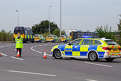 © Licensed to London News Pictures. 13/09/2021. Staines, UK. A police officer directs traffic as protesters from climate campaign 'Insulate Britain', an offshoot of Extinction Rebellion (XR), block the clockwise slip road at Poyle Interchange/junction 14, M25 London Orbital Motorway. Photo credit: Peter Manning/LNP