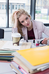 Portrait of businesswoman feels board in office and puts on make up