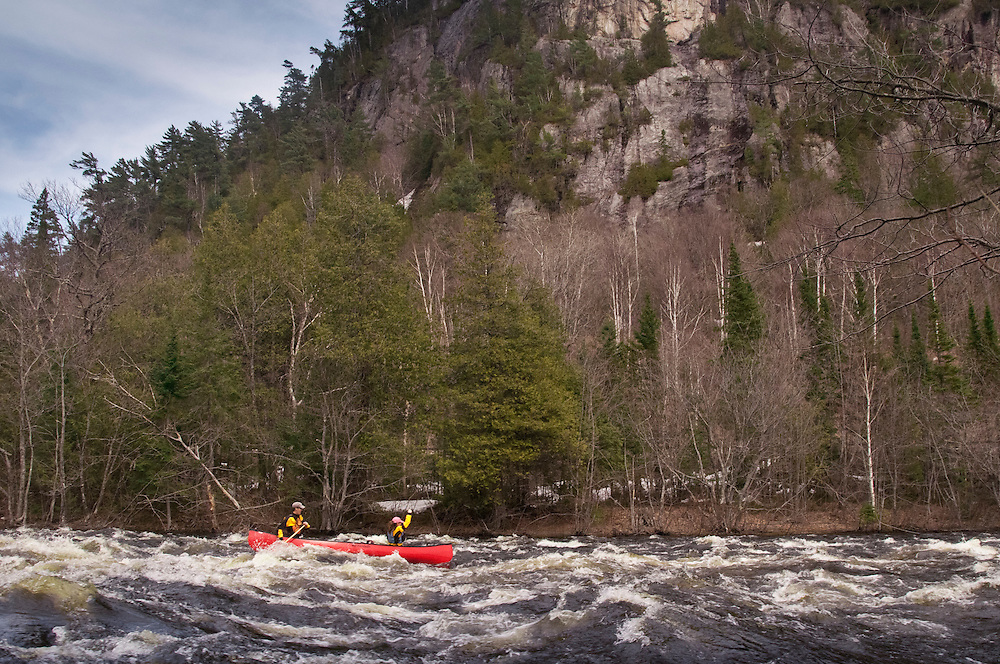 Canoeists run a Class II whitewater rapid on the Agawa River of Ontario Canada.