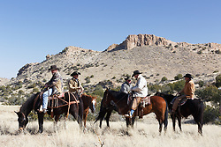Cowboys on horseback during bison roundup, Ladder Ranch, west of Truth or Consequences, New Mexico, USA.