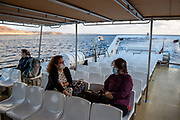Two women in face masks chat on a nearly empty ferry to La Graziosa Island off the coast of Lanzarote, Spain on 23rd November 2020. Beaches and resorts across the island are nearly deserted since tourism plummeted due to Covid restrictions elsewhere in Europe. Although the Canary Islands have been relatively unscathed by the virus, with 155 lives lost from 2.1 million residents, the region is heavily dependent on tourism and locals are hoping that numbers recover as lockdown measures ease and vaccines potentially reduce the numbers of infections.