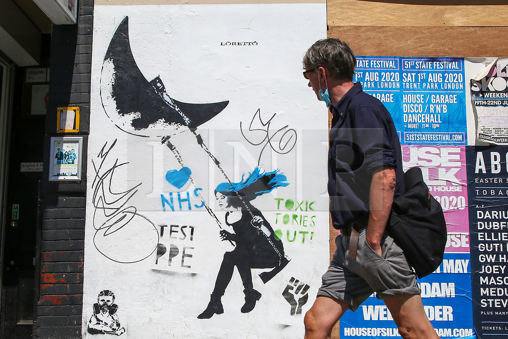 © Licensed to London News Pictures. 30/05/2020. London, UK. A man walks past a painted graffiti wall with a message 'NHS, TEST PEP and TOXIC TORIES OUT!' in north London as coronavirus lockdown restrictions are eased. Photo credit: Dinendra Haria/LNP