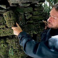 PERU. Dr. Peter Lerche (MR) examines Chachapoyan (pre-Incan) artifact at previously undiscovered site in Peruvian cloud forest above Rio Huabayacu.