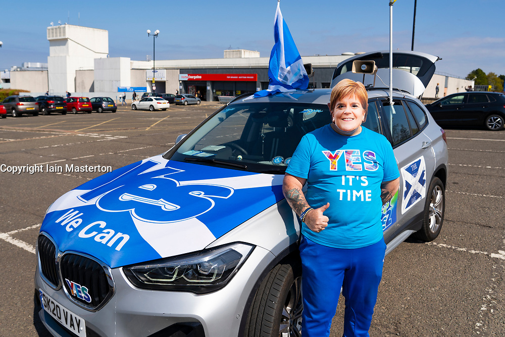 Edinburgh, Scotland, UK. 24 April 2021. Campaigner for the SNP party wears mask of Nicola Sturgeon when posing beside SNP ad van Wester Hailes in Edinburgh today. Iain Masterton/Alamy Live News