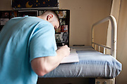 An enhanced prisoner  writing a letter home in his cell on H wing at YOI Aylesbury.