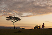 A Maasai man with an old replica safari vehicle near Cottars 1920s Camp in Cottars Conservancy, Kenya