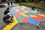 Edward Jones employees paint a gigantic map of the United States on the playground at Highland Elementary School. Volunteers from the Pacific Life Foundation, Edward Jones, the Riverview Gardens School District, the Boys & Girls Clubs of Greater St. Louis and the community joined KaBOOM! and transformed an empty site into a kid-designed, state-of-the-art playground at Highland Elementary School on Saturday August 18, 2018. The playground - designed from students' drawings - will give more than 400 kids a safe place to play. KaBOOM! is a national non-profit dedicated to bringing balanced and active play into the daily lives of all kids.  Photo by Tim Vizer