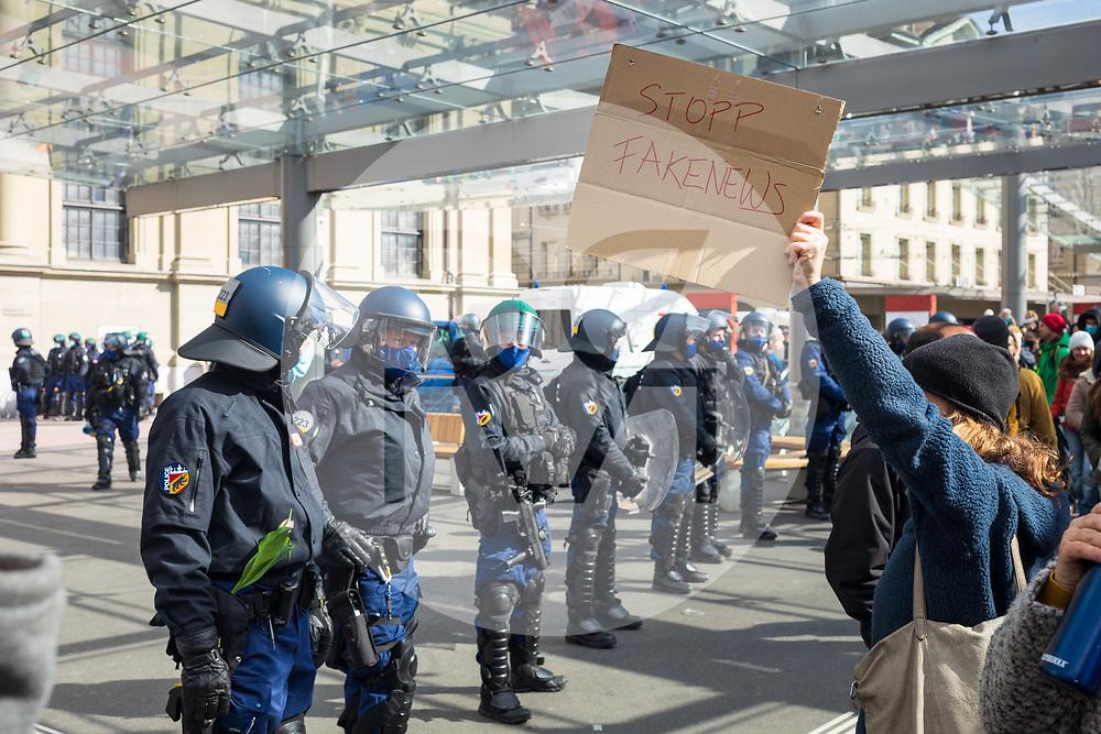 SCHWEIZ - BERN - Demonstrationsschild 'Stopp Fakenews' und ein Polizist mit einer Tulpe im Gurt, welche er von einer Demonstrantin geschenkt bekommen hatte, auf dem Bahnhofsplatz. Die Polizei kesselt eine Kundgebung ein und löst diese später auf. Während einer unbewilligten Demonstration gegen die Massnahmen zur Eindämmung der Corona-Pandemie - 20. März 2021 © Raphael Hünerfauth - https://www.huenerfauth.ch