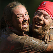 A couple embrace after tackling the mud pit during the New York Merrell Down and Dirty Obstacle Race presented by Subaru. Over 6000 competitors took part in the event which included mud pits, water crossings, slippery mountain, cargo nets, monster climb and ladder walls. The event was held at Pelham Bay Park The Bronx, New York. 29th September 2013. Photo Tim Clayton