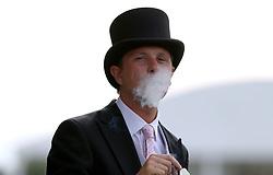 A racegoer enjoys a cigar during day five of Royal Ascot at Ascot Racecourse.