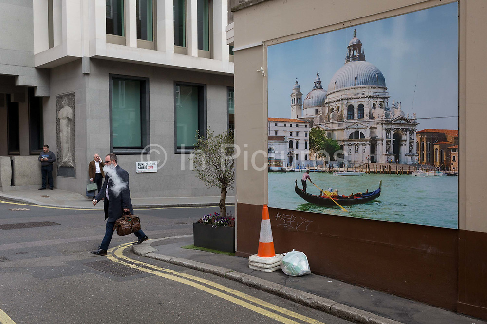 A vaping man strides past a wall picture showing a gondolier and the church of Santa Maria della Salute church in Venice, on 16th March 2017, on the corner of Duke of York Street, in St jamess, London, England.