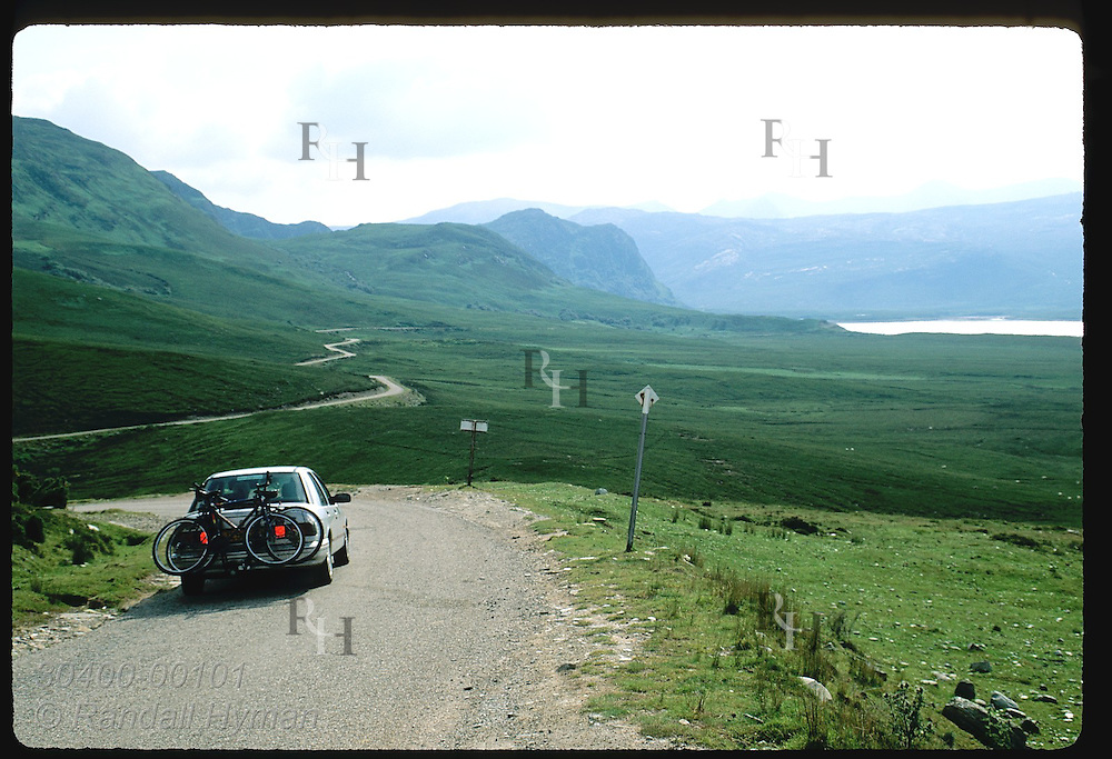 Car brakes as it corners curve on remote road along west coast of Scotland; Kyle of Durness. Scotland