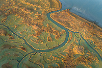 Aerial view of small river crossing wetland during sunset, Netherlands.