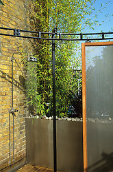 Outdoor shower on roof terrace with sliding wire mesh screen. Design: Diarmuid Gavin