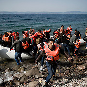A group of Syrian refugees, the moment they disembark from their small inflatable boat and land to Europe, on the beach of Skala Sykaminias. <br /> <br /> Everyday hundreds of refugees, mainly from Syria and Afghanistan, are crossing in small overcrowded inflatable boats the 6 mile channel from the Turkish coast to the island of Lesbos in Greece. Many spend their life savings, over $1000, to buy a space on those boats.