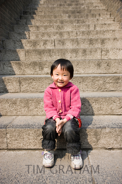Young girl sits on steps at the Small Wild Goose Pagoda, Xian. China has a one child policy to limit population.