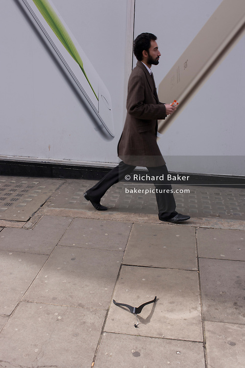 Apple iPhone ad, striding pedestrian and bent fashion retailer hanger dropped on a central London side street.