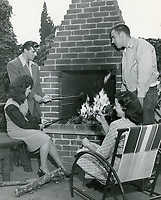 1952 Two YWCA members and their guests roasting marshmallows at the YWCA clubhouse at 6927 Hawthorn St.