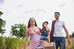 Family with picnic basket walking on meadow and smiling, Bavaria, Germany