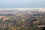 Aerial view of coastline near Faro, Algarve, Portugal showing settlements on coastal plain and offshore sand banks with sandy beaches running along the coast