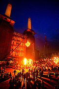 The Fire Garden, a performance delivered by the French performance group Carabosse, commisioned by Totally Thames, was an illuminating, artistic tribute, delivered on a monumental scale, to Battersea Power Station before it is closed for redevelopment. This was fire alchemy at its very best: the smell of wax, the hiss of steam, and the heat and glow of the multiple fires acknowledging and celebrating this iconic site's gritty, smoke belching, industrial past. Globes of fire and thousands of points of flickering flame illuminate the Power Station as musicians play a mix of old style Parisian music with moody improvised sounds. Battersea Power Station is a decommissioned (1983) coal-fired power station located on the south bank of the River Thames, in Battersea, an inner-city district of South West London. It comprises two individual power stations, built in two stages in the form of a single building.