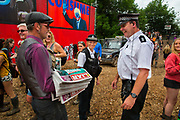 Selling the Shangri Liar, an ironic tabloit style newspaper raising money for the refugee kitchens in Calais and Dunkirk, to a policeman patrolling the Shangri La field, Glastonbury Festival 2016. The Glastonbury Festival is the largest greenfield festival in the world, and is now attended by around 175,000 people. Its a five-day music festival that takes place near Pilton, Somerset, United Kingdom. In addition to contemporary music, the festival hosts dance, comedy, theatre, circus, cabaret, and other arts. Held at Worthy Farm in Pilton, leading pop and rock artists have headlined, alongside thousands of others appearing on smaller stages and performance areas.