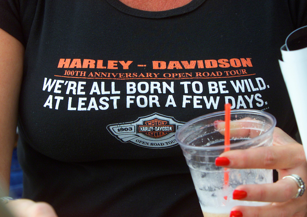 A woman sports a tee-shirt commemorating the 100th anniversary of the legendary American motorcycle company Harley-Davidson in Milwaukee August 28, 2003. The firm begins it's four-day celebration beginning today. REUTERS/Rick Wilking