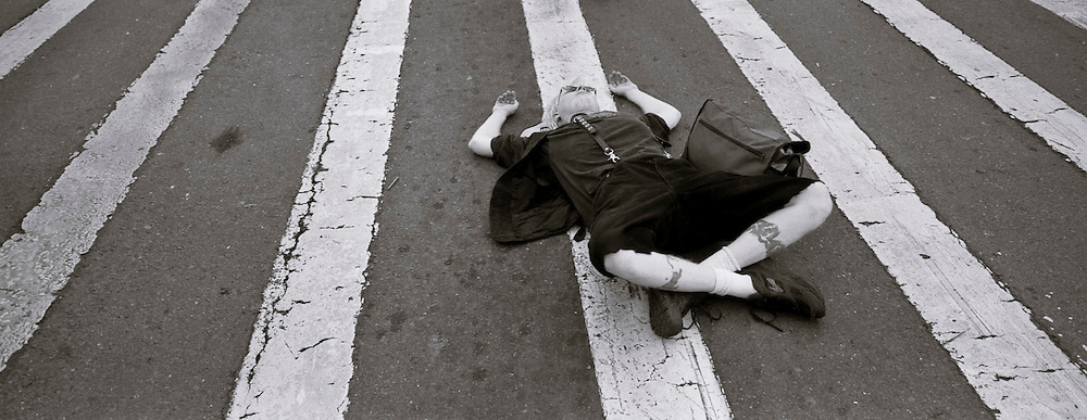 A demonstrator at Occupy Oakland pauses to rest on a crosswalk next to Frank Ogawa Plaza.