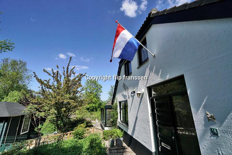 Nederland, Ubbergen, 5-5-2020 Aan de gevel van een huis hangt de nederlandse valg strak te wapperen tegen een blauwe lucht. Het is nationale bevrijdingsdag. Dit jaar een feest zonder evenementen vanwege de coronamaatregelen . FOTO: FLIP FRANSSEN