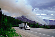 Articulated truck driving past the smoke of a forest fire in Canada