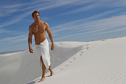 great looking man wearing only a white towel walking on top of a sand dune in White Sands, NM